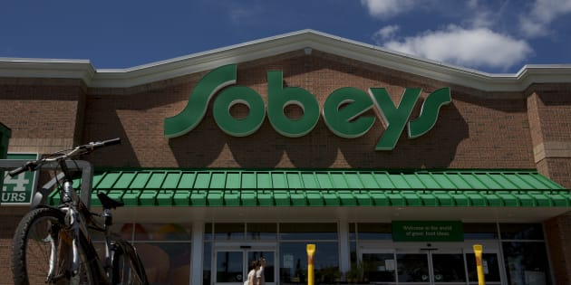 Pedestrians pass in front of a Sobeys Inc. grocery store in Toronto on July 24, 2013.