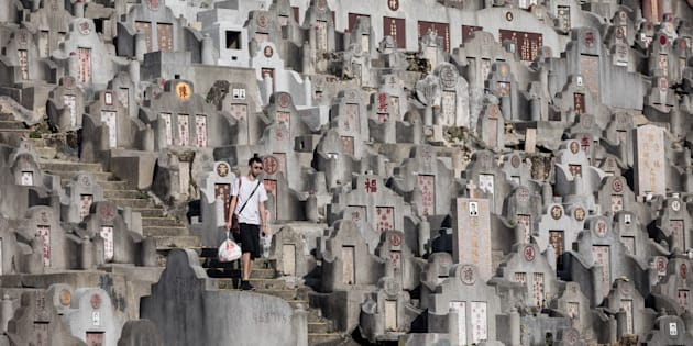 A man walks past tombstones at a cemetery ahead of the Ching Ming Festival, or grave-sweeping day, in Hong Kong.