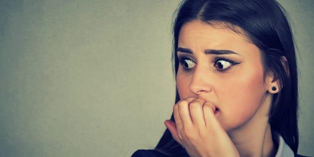 Una mujer ansiosa mordiendo sus uñas.