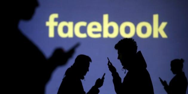 Las siluetas de los usuarios de dispositivos móviles se ven al lado de una proyección en pantalla del logotipo de Facebook.