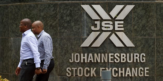 Workers pass a sign outside the headquarters of the Johannesburg Stock Exchange (JSE) in the Sandton district of Johannesburg, South Africa, on Thursday, Dec. 19, 2013.