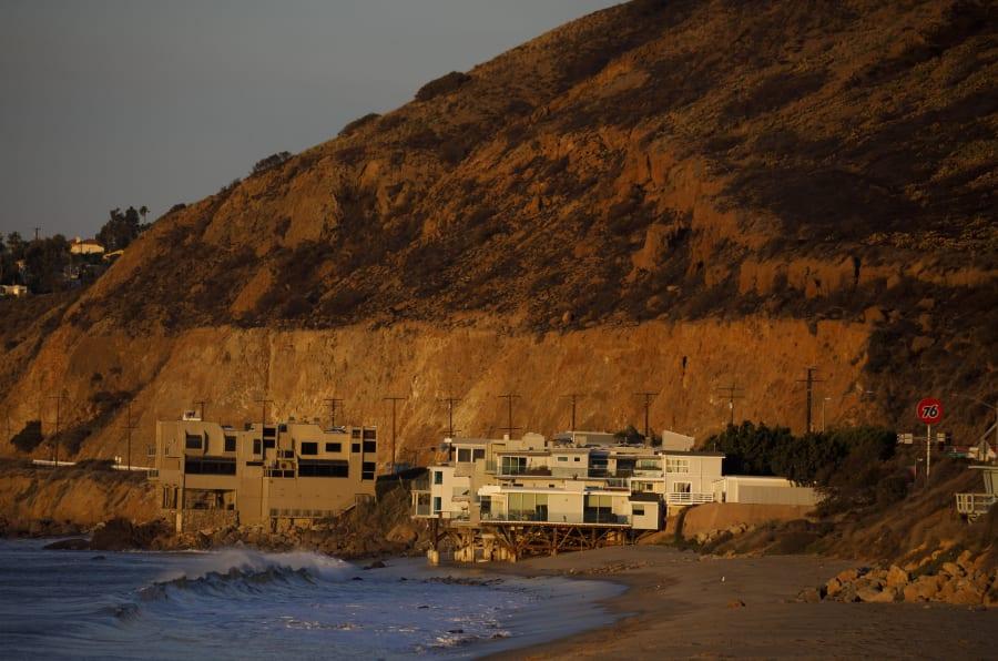 Des maisons au bord de l'océan au-dessous d'une colline brûlée lors de l'incendie de Woolsey à Malibu, en Californie, le 13 novembre 2018.