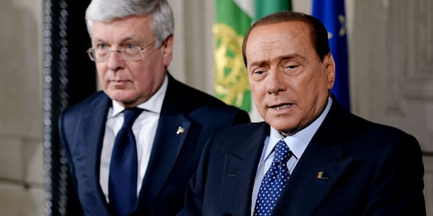 Former Prime Minister Silvio Berlusconi (R) flanked by former minister Paolo Romani (L) speaks after meeting with Italian president Giorgio Napolitano at the Quirinale palace in Rome on February 15, 2014. Florence mayor Matteo Renzi was poised to win the nomination to be Italy's youngest-ever prime minister on February 15 following the ouster of Enrico Letta by former allies in his centre-left Democratic Party. President Giorgio Napolitano was set to appoint Renzi after a day of consultations with political leaders including disgraced former premier and opposition leader Silvio Berlusconi. AFP PHOTO / FILIPPO MONTEFORTE        (Photo credit should read FILIPPO MONTEFORTE/AFP/Getty Images)