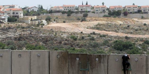 Un palestino se asoma por encima del muro de Cisjordania, a la altura de Nilin, con una colonia israelí al fondo.