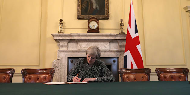 British Prime Minister Theresa May in the cabinet, sitting below a painting of Britain's first Prime Minister Robert Walpole, signs the official letter to European Council President Donald Tusk invoking Article 50 and the United Kingdom's intention to leave the EU on March 28, 2017 in London, England. After holding a referendum in June 2016 the United Kingdom voted to leave the European Union, the signing of Article 50 now officially triggers that process. REUTERS/Christopher Furlong/Pool