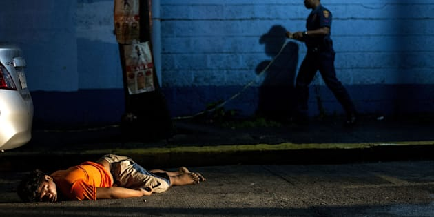 The body of a man, shot dead by unidentified gunmen, lies on the ground in Manila on July 23, 2016.
