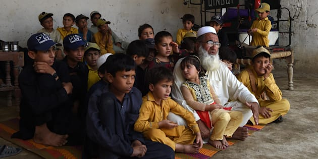 In this photograph taken on May 20, 2017, Pakistani father Gulzar Khan, 57, who has 36 children from his three wives, sits with his children as he speaks during an interview with AFP at his house in the northwestern town of Bannu.