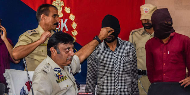 Muneer Ahmed Khan, Inspector General of police Kashmir, shows Sandeep Kumar, a Hindu non-local, militant  during a  press conference at a police head quarter on July 10, 2017 in Srinagar.