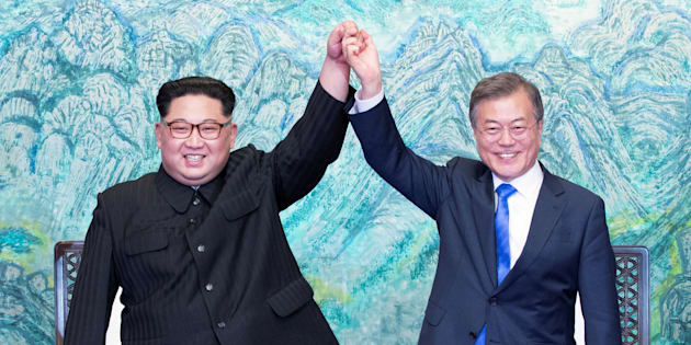 South Korean President Moon Jae-in and North Korean leader Kim Jong Un raise their hands at the truce village of Panmunjom inside the demilitarized zone separating the two Koreas, South Korea, April 27, 2018.   Korea Summit Press Pool/Pool via Reuters