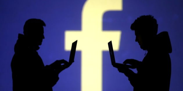 Silhouettes of laptop users are seen next to a screen projection of Facebook logo in this picture illustration taken March 28, 2018. A U.S. federal judge ruled on Monday that Facebook must face a class action lawsuit alleging that the social network unlawfully used a facial recognition process on photos without user permission.