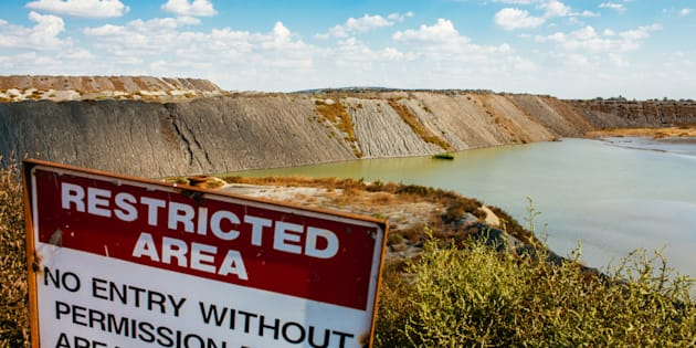 A restricted area warning sign sits on the site of old kimberlite rock tailings beside a water filled excavation pit at the Voorspoed diamond mine, operated by De Beers SA, in Kroonstad, South Africa, on Tuesday, May 3, 2017. The Anglo American Plc unit plans to store carbon-dioxide in kimberlite -- a type of ore best known for containing diamonds, but which also naturally reacts with carbon to remove it from the atmosphere. Photographer: Waldo Swiegers/Bloomberg via Getty Images
