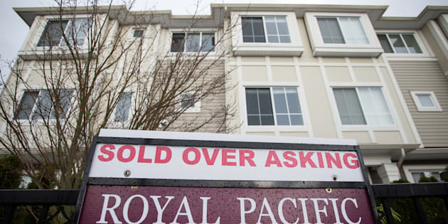 """A  """"sold over asking"""" outside a townhouse in Richmond, British Columbia, Canada, on Sunday, Dec. 11, 2016. Greater Vancouver is still seeing rising home prices, despite a cooling-off of sales over the past year."""