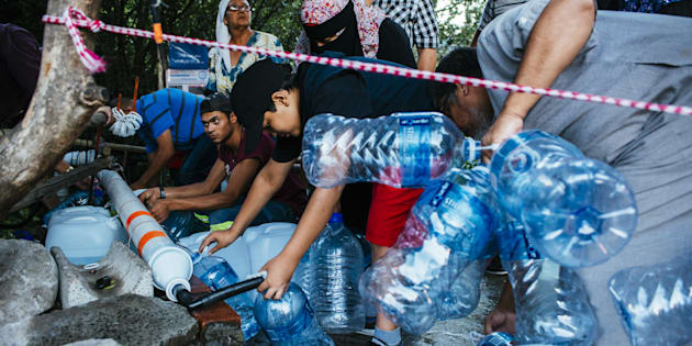 Residents collect water from a pipe to fill plastic water bottles at the Newlands natural water spring in Cape Town, South Africa, on Wednesday, Feb. 7, 2018.