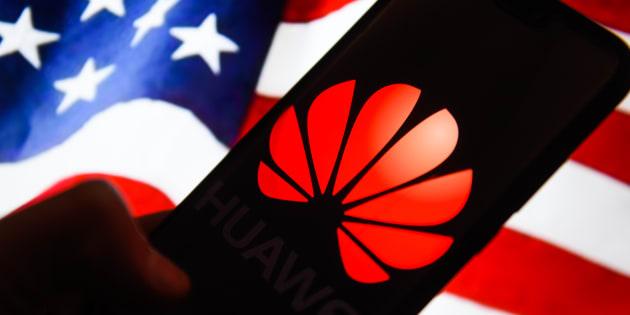 El logotipo de Huawei se ve en un teléfono móvil Android con la bandera de Estados Unidos en el fondo.