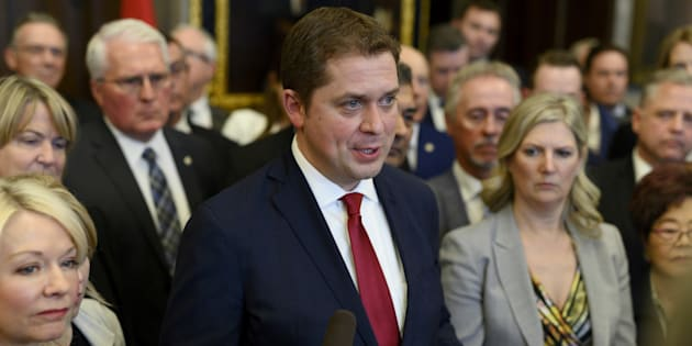 Conservative Leader Andrew Scheer speaks to reporters with his caucus surrounding him after leaving the finance minister's budget speech in protest to the handling of the SNC Lavalin scandal, in Ottawa on March 19, 2019.