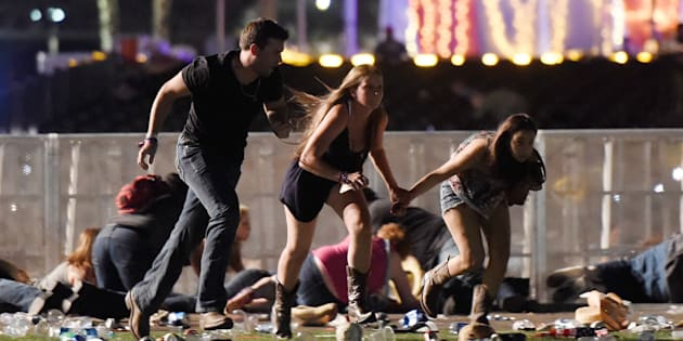 Festivalgoers run from the Route 91 Harvest country music festival in Las Vegas, Nevada, after gunfire was heard on October 1 2017.