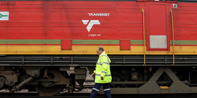 Jacobus van der Merwe, a train driver, passes a locomotive operated by Transnet at the company's rail depot in Ermelo, March 10, 2014.
