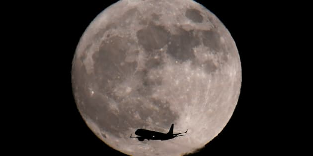 A passenger plane, with a 'supermoon' full moon seen behind, makes its final landing approach towards Heathrow Airport in London, Britain, January 1, 2018.