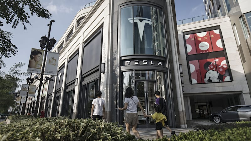 pedestrians-walk-past-a-tesla-inc-showroom-in-shanghai-china-on-sept-picture-id848763298