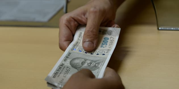 A bank staff member hands Indian 500 rupee notes to a customer on November 24, 2016, in the wake of the demonetisation of old 500 and 1000 rupee notes in Mumbai.