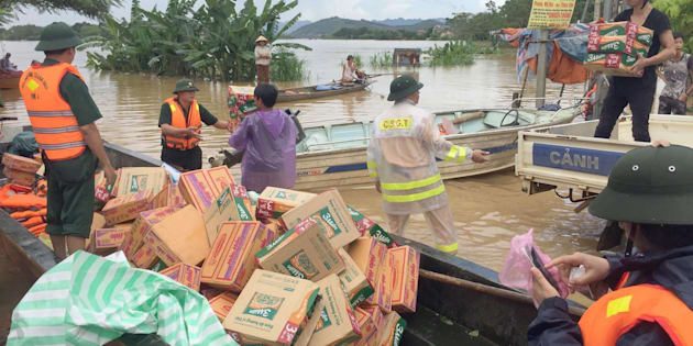 Rescuers load boats with boxes of foods, mostly instant noodles, that will be distributed to local residents in Thach Thanh district, central province of Thanh Hoa on October 12, 2017.