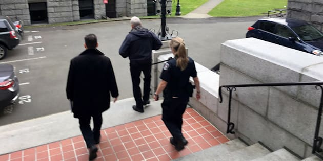 B.C. legislature sergeant-at-arms Gary Lenz is escorted out of the legislature by security in Victoria, B.C. on Nov. 20, 2018.