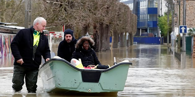 Municipal employees assist a resident who sits in a boat as the Marne River overflows its banks in Gournay-sur-Marne, near Paris, France, February 2, 2018.   REUTERS/Gonzalo Fuentes
