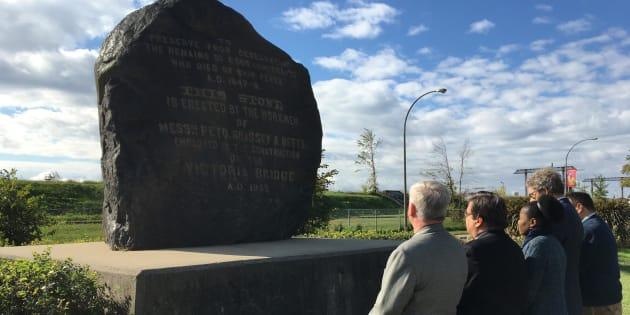 Denis Coderre se recueille devant le monument Black Rock avec des membres de son équipe.