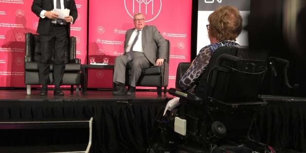 Lise Pigeon, en chaise roulante, et  le ministre Gaétan Barrette sur la scène.