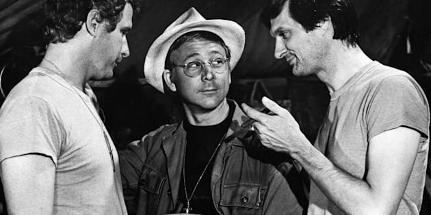 "William Christopher, center, as Father Mulcahy on ""M.A.S.H."" surrounded by co-stars Wayne Rogers as Trapper John (left) and Alan Alda as Benjamin Franklin ""Hawkeye"" Pierce (right)."