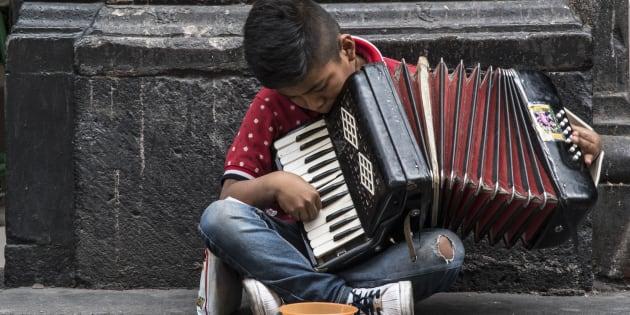 En la imagen un niño en la calle Madero toca el acordeón a cambio de monedas como forma de sustento.