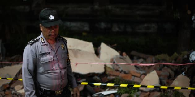 Un policier devant les ruines d'un immeuble à Bali, après le nouveau séisme à Lombok, le 5 août.