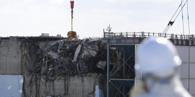 Un periodista se cubre la cara ante el reactor 3 de la central siniestrada.