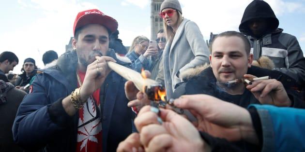 A man smokes marijuana during the annual 4/20 marijuana rally on Parliament Hill on April 20, 2018.