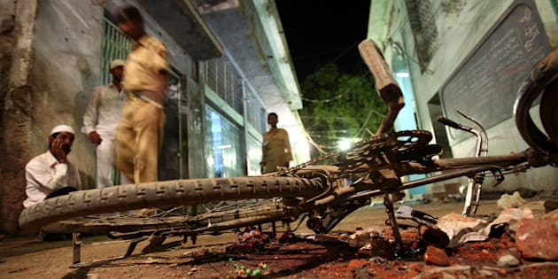 [FILE PHOTO] People walk past a damaged bicycle lying at a blast site inside a mosque in Malegaon on September 9, 2006.