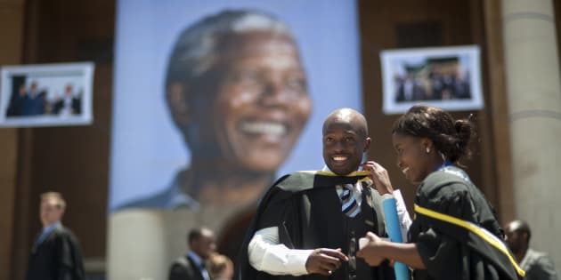 Students celebrate their graduation ceremony on the steps of Cape Town University where a giant picture of Nelson Mandela hangs down on December 13 2013, in Cape Town.
