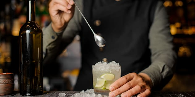Barman stirring cachaca with lime and ice in the glass making Caipirinha cocktail on the bar counter