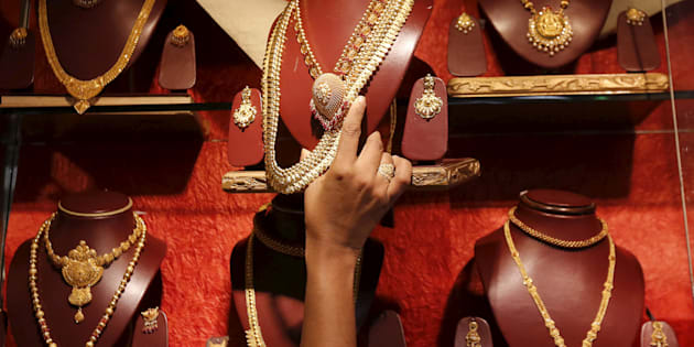 A saleswoman keeps a gold necklace in a shelf at a showroom in Mumbai, India, August 13, 2015.