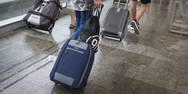 Personas con maletas en un aeropuerto español.