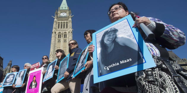 Women hold images of murdered and missing indigenous women during a rally for Missing and Murdered Indigenous Women on Parliament Hill in Ottawa, Tuesday October 4, 2016. THE CANADIAN PRESS/Adrian Wyld