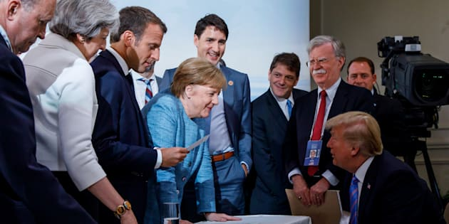 Prime Minister Justin Trudeau, British Prime Minister Theresa May, French President Emmanuel Macron, German Chancellor Angela Merkel, and U.S. President Donald Trump discuss the joint statement following a breakfast meeting at the G7 summit in La Malbaie, Que. on June 9, 2018.