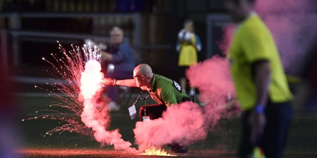 A security guard picks up a flare that was thrown onto the field during second half Canadian Championship soccer action between the Ottawa Fury FC and the Toronto FC in Ottawa on July 18, 2018.