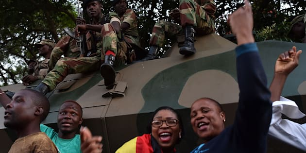 People celebrate next to soldiers in the streets of Harare, after the resignation of Zimbabwe's former president Robert Mugabe on November 21, 2017.