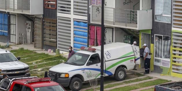Personal forense introduce en una camioneta uno de los cuerpos rescatados dentro de un departamento en Villa Fontana Aqua en Tlajomulco, Jalisco.