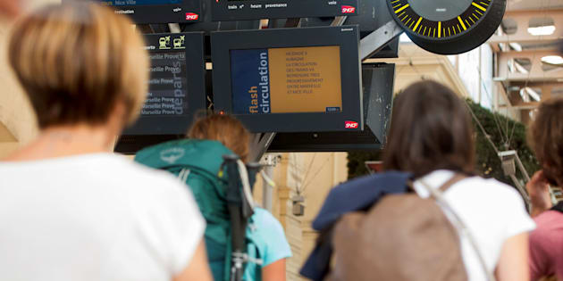 Passengers look at information monitors as they wait for their trains at The Saint-Charles Station in Marseille on August 20.