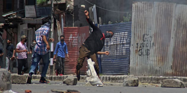 SRINAGAR, JAMMU AND KASHMIR, INDIA - 2017/05/27: A masked youth throwing stone towards government forces in Srinagar May 27, 2017 .  Civilian was killed and dozens of others injured in Indian-controlled Kashmir following the killing of a top militant commander and his associate during a  gunbattle with government forces. (Photo by Umer Asif/Pacific Press/LightRocket via Getty Images)