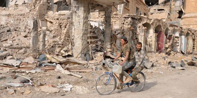 Unos hombres pasan en bicicleta ante las ruinas de un edificio en Deir Ezzor, el pasado noviembre.