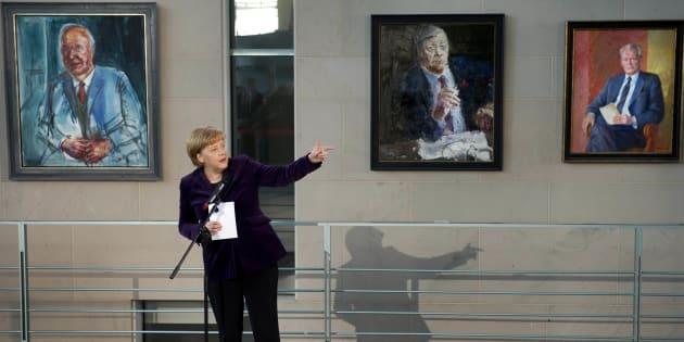 La chancelière Angela Merkel devant les portraits de précédents chanceliers, de gauche à droite Helmut Kohl, Helmut Schmidt et Willy Brandt, à la Chancellerie fédérale à Berlin, le 5 janvier 2011.
