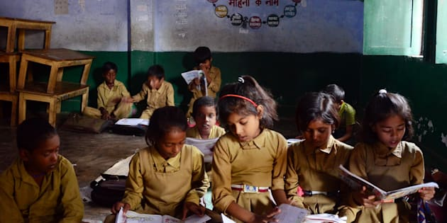 School children reading books while inside the classroom at a government-run school.