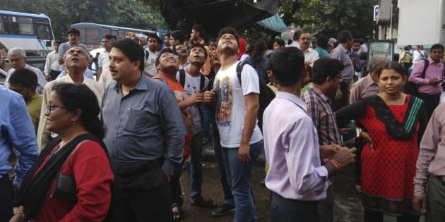People stand outside their offices after they rushed outdoors following tremors in Kolkata, India.